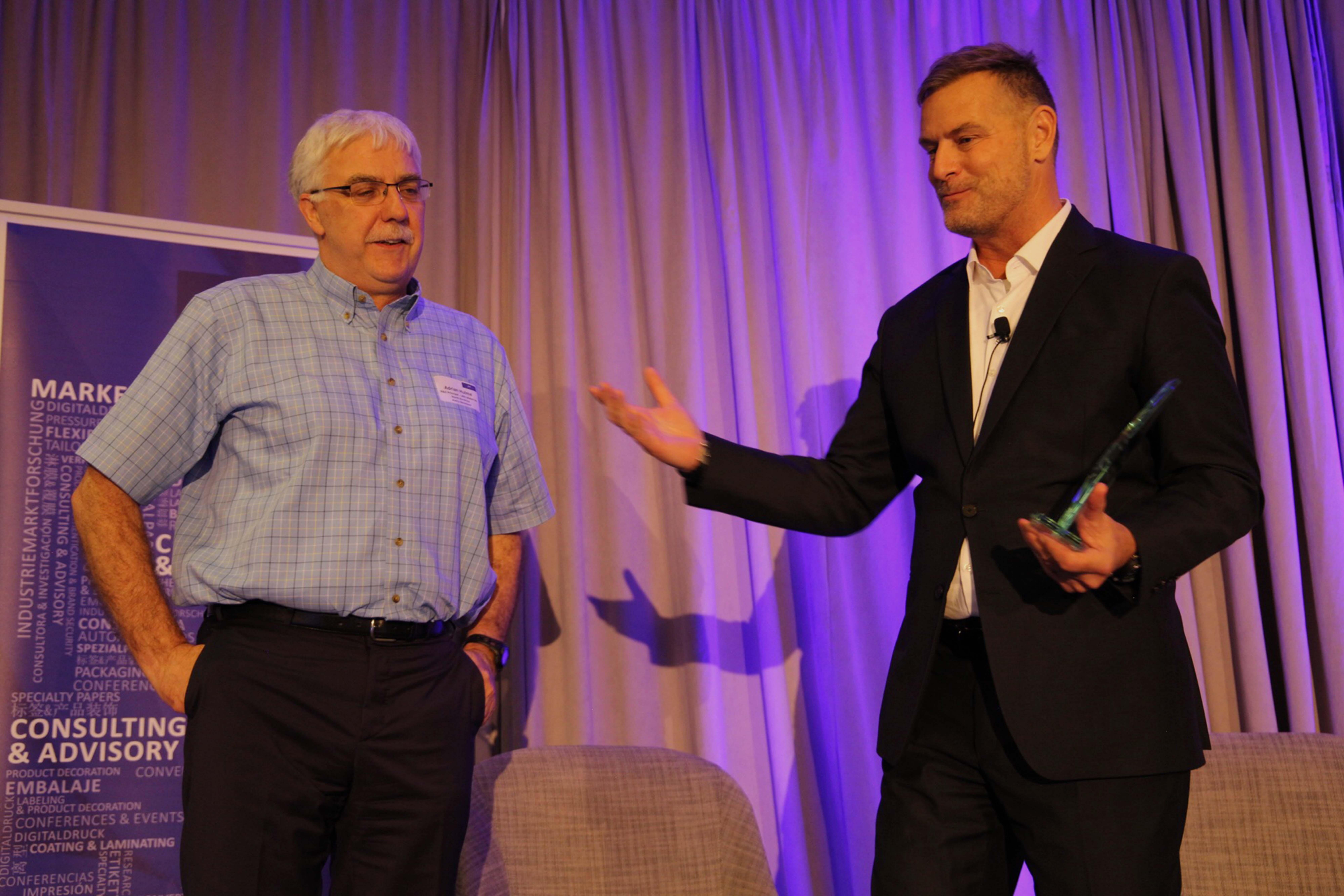 Adrian Hulme, Avery Dennison(left), receives the AWA Release Liner Industry Leadership Award from Corey Reardon, AWA Alexander Watson Associates.